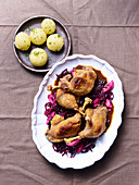 Confit duck legs on red cabbage with potato dumplings