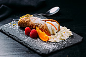 Board with fried and folded pancake filled with whipped cream and served with raspberry