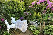 Kleine Terrasse mit Sitzplatz neben Rhododendron