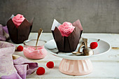 Delicious frosting cupcakes decorated with pink cream cheese and raspberry