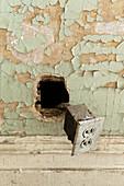 Alte Steckdose hängt aus der Wand mit abgeblätterter Farbe