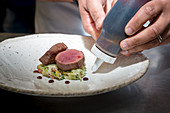 A lamb fillet dish being plated