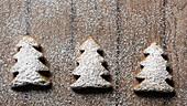Drei Lebkuchenplätzchen in Weihnachtsbaumform mit Puderzucker