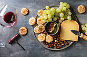 Cheese, grapes, nuts, cheese crackers cookies, honeycombs with laying glass of red wine and knife over dark background