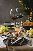 Dinner table set with wine, cheese plate, appetizers, lightning garland, xmas decoration
