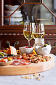 Chacuterie-Platte mit Wurst, Käse, Knabbereien und Weißwein