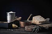 Stillleben mit Zutaten und Utensilien für Risotto vor schwarzem Hintergrund