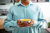 Mann hält eine Schale Cerealien mit Obst, Joghurt und Samen