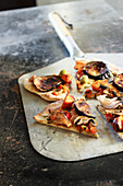 Eggplant pizza with mushrooms, olives, red pepper, red onion and roasted carrot topping