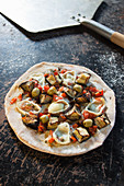 Stoned eggplant pizza with mushrooms, olives, red pepper, red onion and goat's cheese