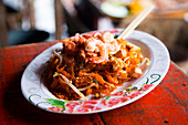 Traditional Pad Thai dish, served in a street food stand in Tha Kha Floating Market, Samunt Songkhram Province in Thailand