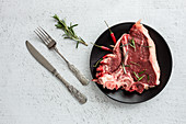 Raw beef steak with rosemary and chilli peppers
