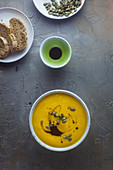 Cream of pumpkin soup with pumpkin seeds and pumpkin seed oil on a grey surface