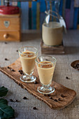 Creamy coffee liqueur in a carafe and served over ice in liqueur glasses