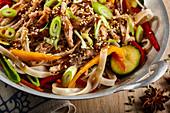 Fried rice noodles with pork belly, vegetables and sesame seeds