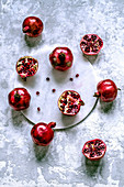 Fresh pomegranates whole and cut with scattered grains on a marble tray