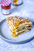 A stack of thin pancakes stacked in four layers with honey and a honey spoon