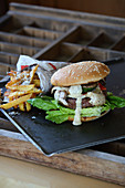 A burger with mushrooms, mayonnaise and chips