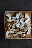 Halved porcini mushrooms in a wooden crate