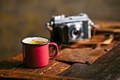 Kaffee in einer Emailtasse und Fotoapparat auf rustikalem Untergrund