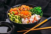 Poke Bowl mit Lachs, Surimi, Edamame und Algen (Asien)