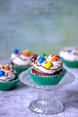 Chocolate cupcakes in green paper forms with butter cream and colored candies