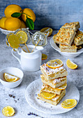 Lemon pie cut by squares, decorated with lemon candies and fresh lemons
