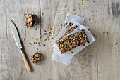 Homemade muesli bars between sheets of paper (seen from above)