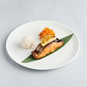 Lachs serviert mit Reis und geraspelten Karotten auf Teller (Japan)
