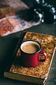 Kaffee im Emaillebecher auf Buch, im Hintergrund Landkarte und Kamera