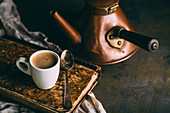 A cup of coffee on an antique book with an old-fashioned copper kettle in the background
