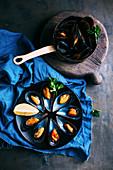 Gekochte Miesmuscheln in Stieltopf und dekorativ arrangiert auf Teller (Aufsicht)