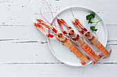Three fresh shrimps lying on plate near sprig of parsley on white timber tabletop