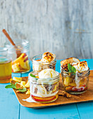 Pineapple and peaches with marshmallows and ice cream in jars