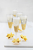 Disposable champagne glasses decorated with gold glitter and star-shaped name cards