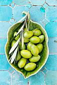 Grüne Oliven mit Zweig in Keramikschale
