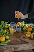 Freshly pressed orange juice and fresh citrus fruits on a rustic wooden table