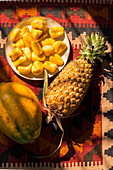 Jackfruit segments on a plate, whole pineapple and papaya on a colourful background