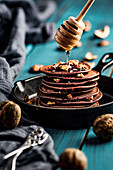 Banana pancakes with cocoa, topped with walnuts and honey