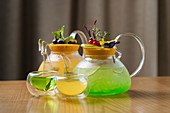 Green and yellow cocktails served in glass jugs and cups