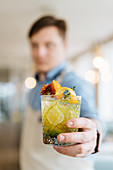 Exotic Nordic cocktail, garnished with flowers in hand of bartender