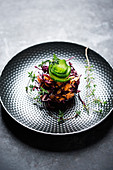 Vegan red cabbage and carrot salad topped with a cucumber spiral