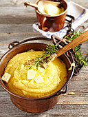 Cooked polenta in a copper kettle with pieces of butter and rosemary