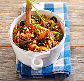 Lukewarm millet and pepper salad with olives and tomato dressing