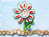 Creative flower made of vegetables as the petals and stalk with rice crackers as the ground