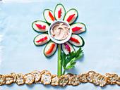 Kreative Blume aus Gemüse mit Hummus und Reiscrackern