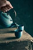 Tee aus asiatischer Teekanne in Teebecher einschenken