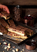 Person Taking A Slice of Millionaires Caramel Shortbread with Dried Fruit and Nuts