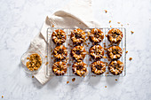 Apfel-Müsli-Donuts mit Zuckerglasur und Granola auf Abkühlgitter (Aufsicht)