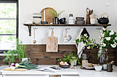 Rustic crockery on shelf in kitchen with wood-clad walls